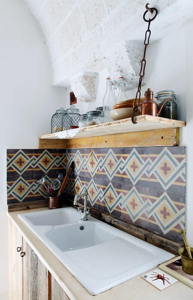 Cocina con azulejos antiguos y repisa de madera con cadenas