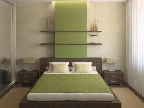 Dormitorio con paredes beige y panel de pared y cama verde, con muebles marrón oscuro