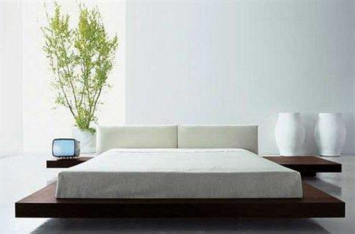 Dormitorio de color blanco con cama de plataforma de madera, y planta decorativa
