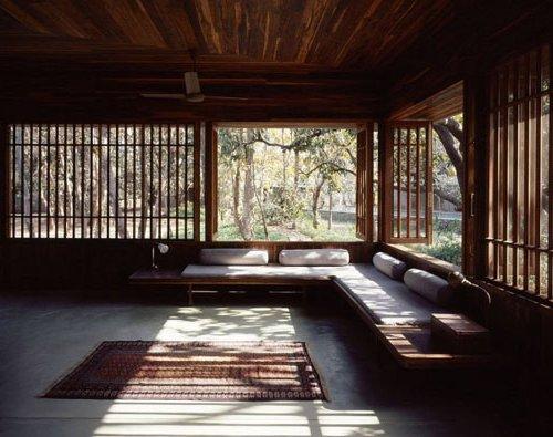 Salón con sillones empotrados en la pared, con amplios ventanales al jardín