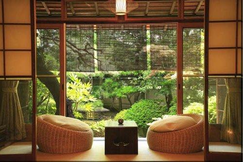 Salón con sillones de ratán y cojines, con ventanal al jardín
