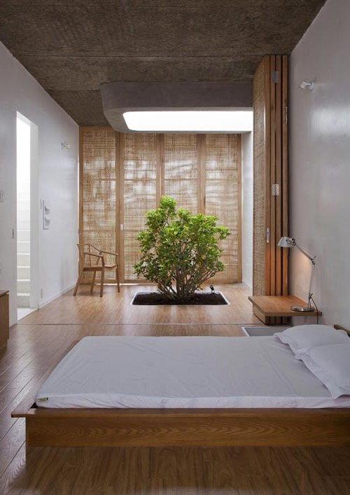 Dormitorio zen con suelos de madera y ventana con cortinas de arpillera, con jardín interior y puerta plegable