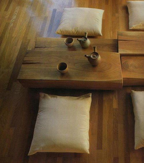 Mesa de madera elaborada en una sola pieza con cojines de lino en el suelo