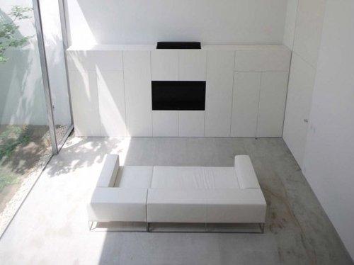 Salón blanco minimalista con sofá y panel en la pared con TV incorporada, amplia ventana al jardín