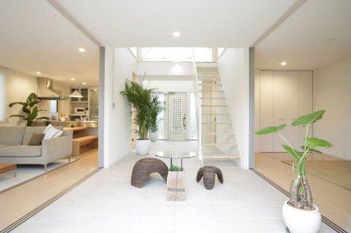 salón con escalera en el centro, decorado en madera y color blanco