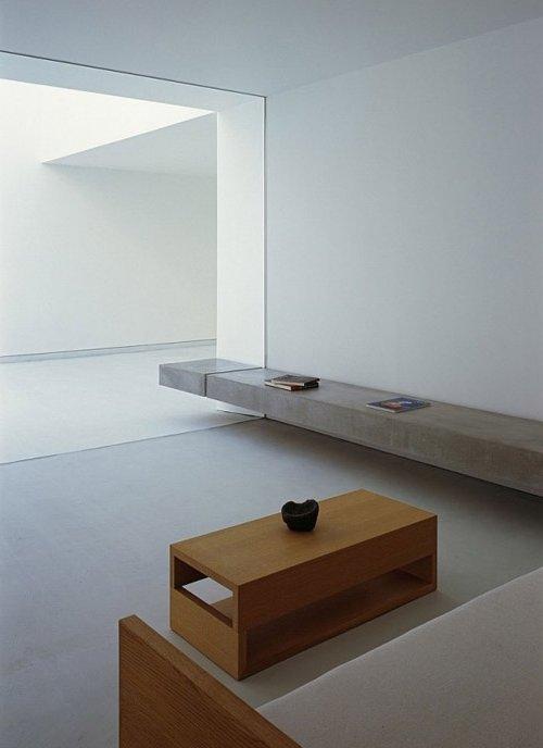 Habitación minimalista ZEN, de color blanco con repisa de cemento y mesita de madera, con amplia ventana de cristal
