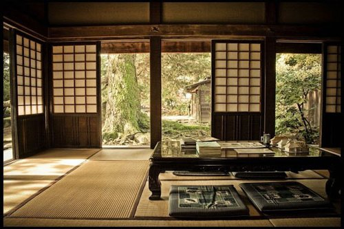 Salón con pantallas corredizas con vistas al jardín. Mesita muy baja con cojines en el suelo y alfombras de bambú