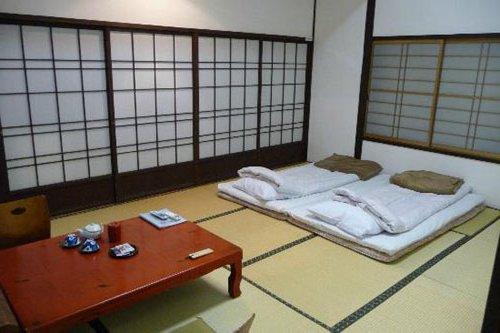 dormitorio con camas futon en el suelo y pantallas japonesas
