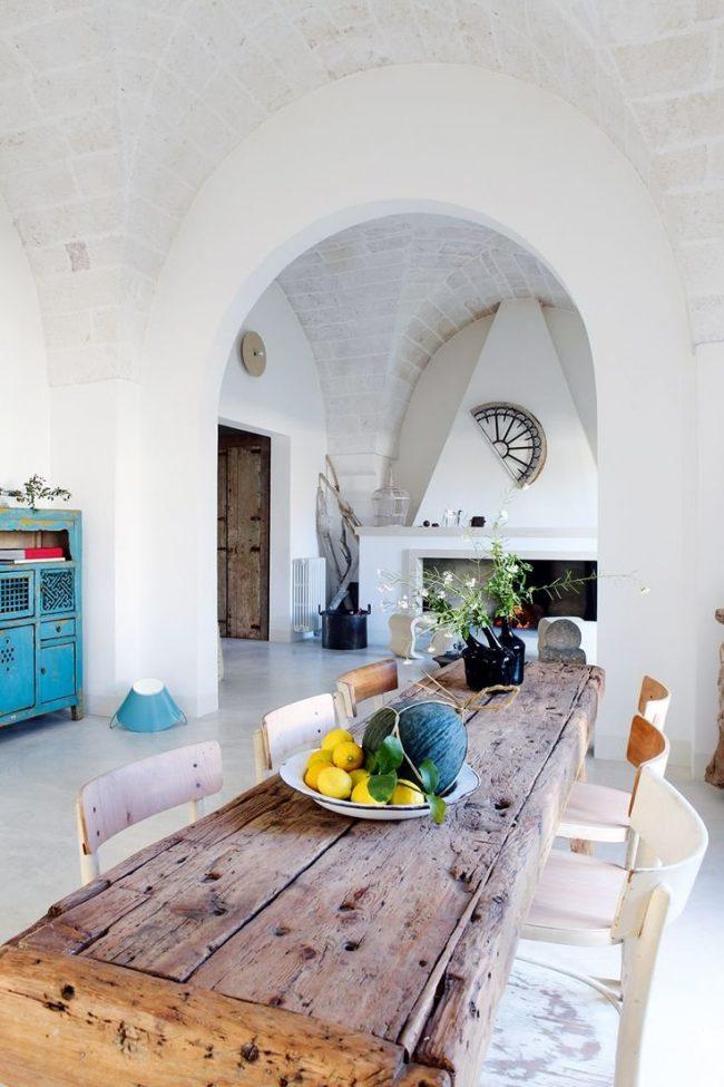 Comedor de paredes y suelo blanco con mesa y sillas rústicas de madera gastada y armario celeste gastado