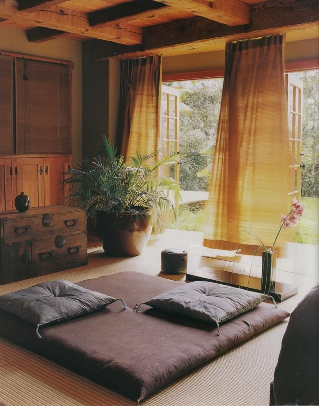 Decoración ZEN en salón con cortinas amarillas, muebles de madera y plantas, con un colchón en el suelo con cojines