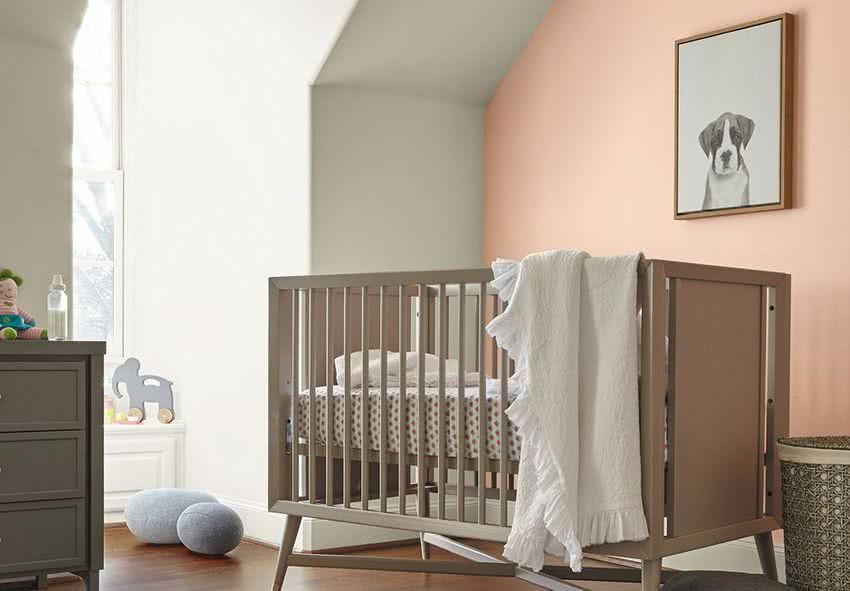 dormitorio bebé, cuna beige, paredes blancas y rosa salmón