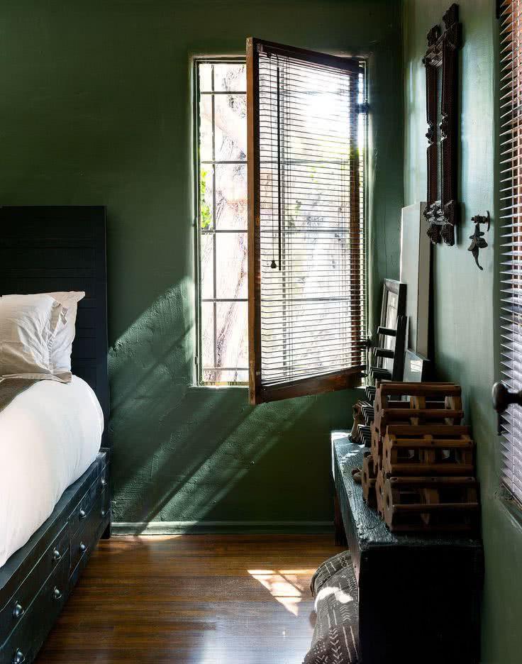 cuarto con paredes verde azulado oscuro, suelos de madera, cama negra
