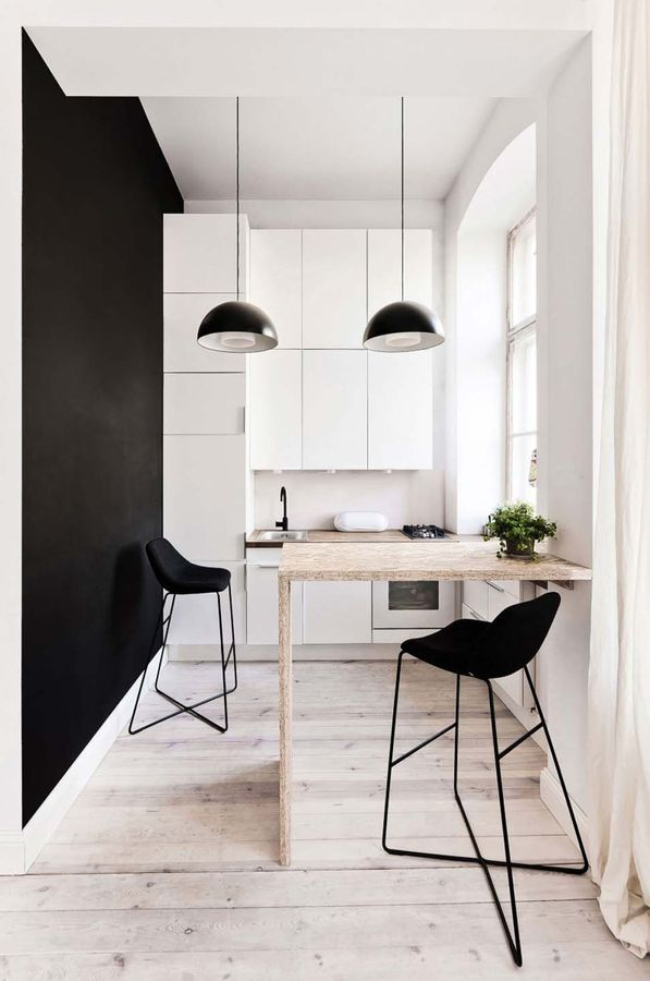 Paredes blancas y negras con mesa americana en madera