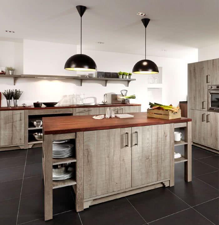 cocina rústica con suelos negros, muebles madera en tonos claros reciclada, encimeras madera más oscura