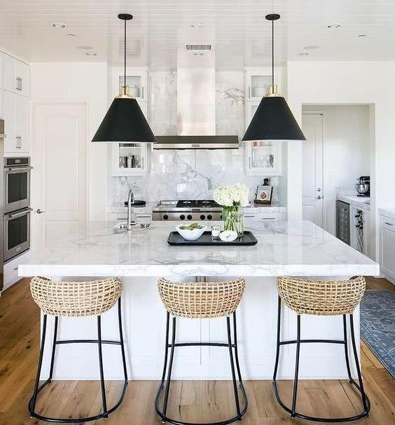 taburetes de ratán y metal oscuro, en cocina blanca y negra