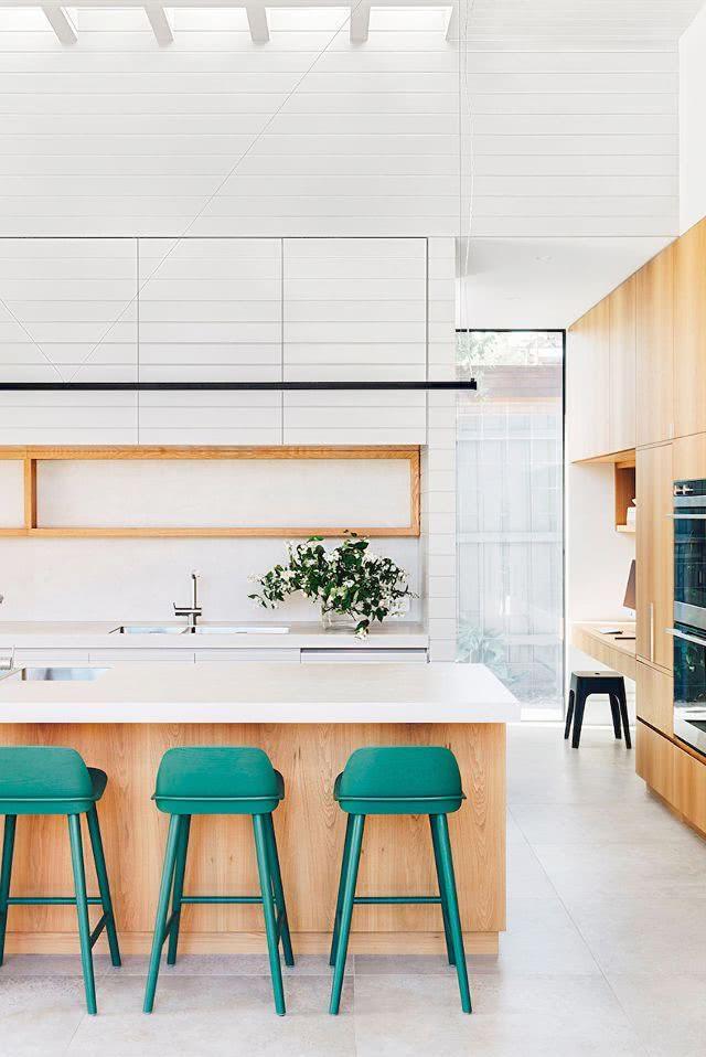 cocina blanca, isla en madera y taburetes color esmeralda