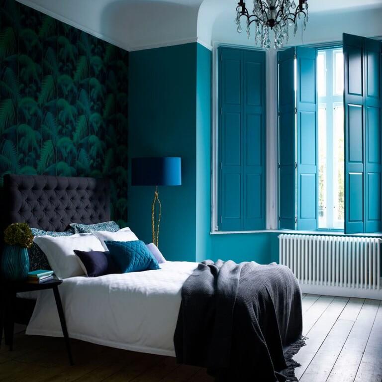 paredes azul intenso, empapelado con vegetación, cama en gris oscuro y blanco, cojines en tonos de azul