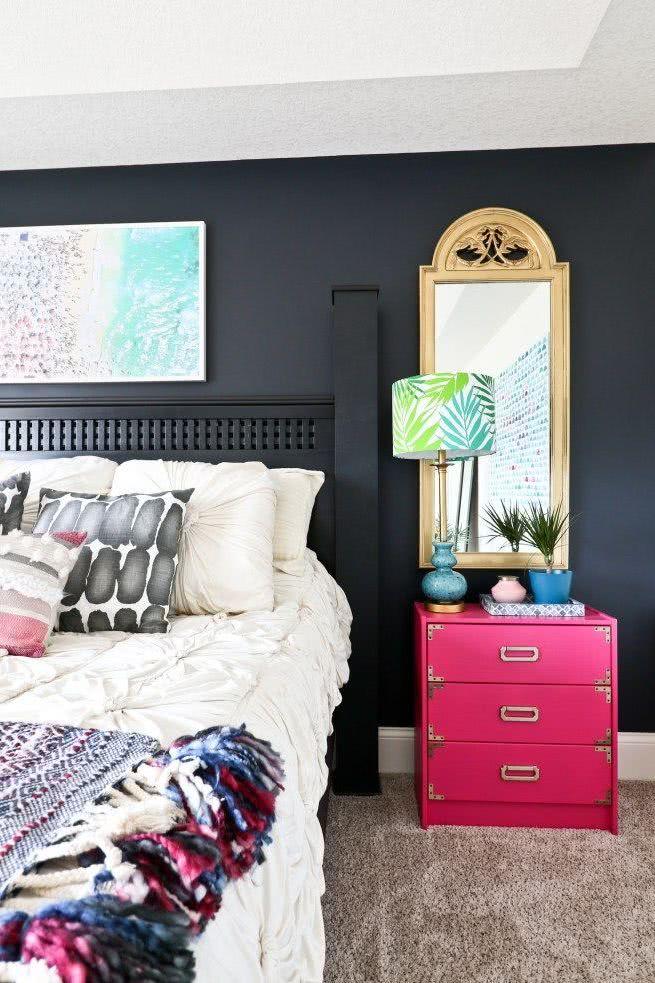 cuarto moderno pared gris oscuro, mesa de noche fucsia, espejo con marco dorado