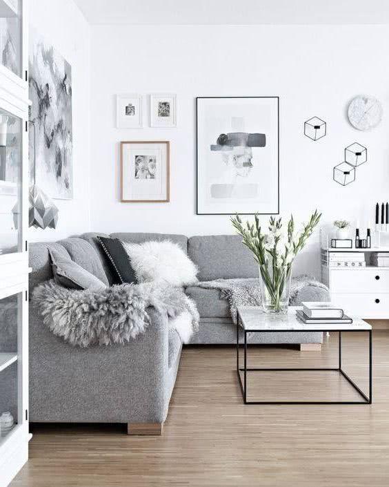 sala paredes blancas con cuadros y sillón moderno gris con cojines