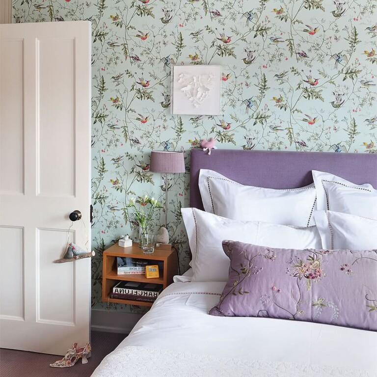 cama decorada con lila y paredes empapeladas con verde menta