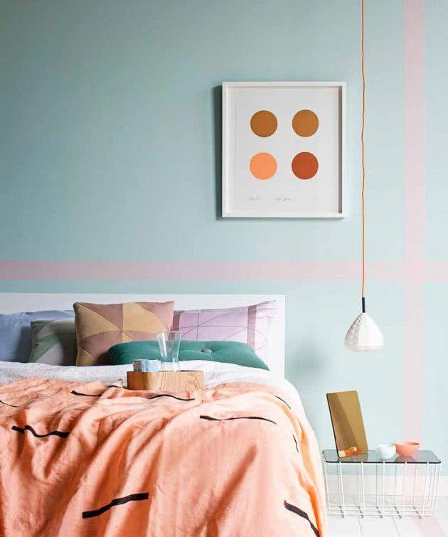 pared celeste con rayas rosa, cama en salmón y cojines coloridos