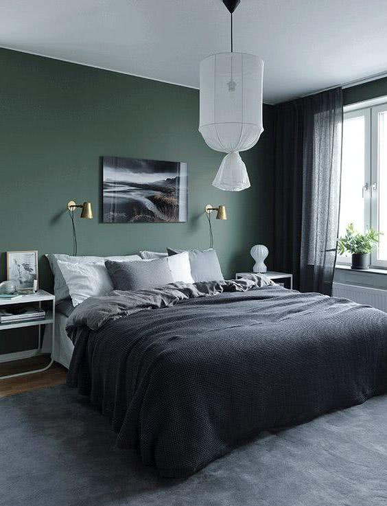 pared verde oscuro cama y decoración gris