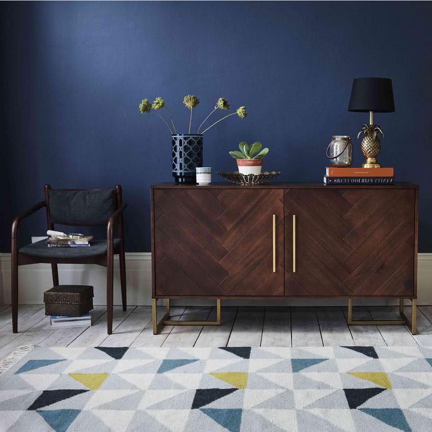 aparador de madera oscura, pared azul marino, alfombra diseños geométricos