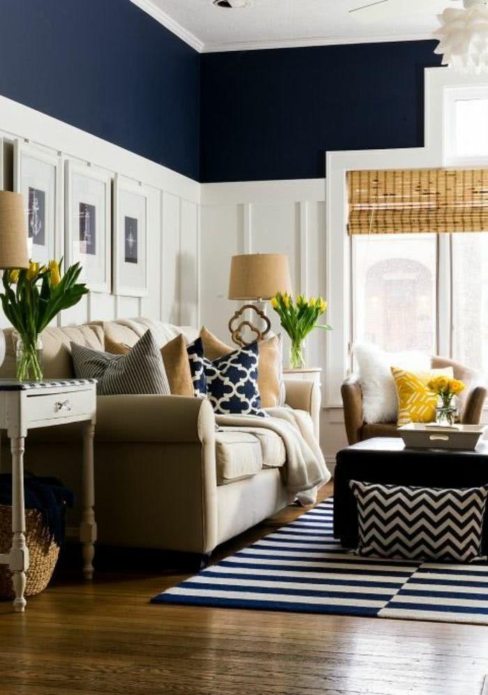 salón paredes en blanco y azul marino, sillón beige, cojines amarillos