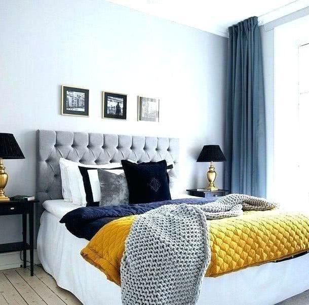 colcha azul y amarillo en habitación decorada de grises