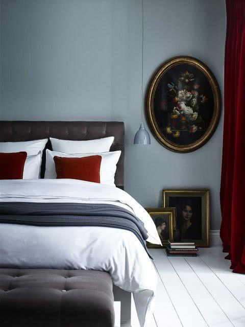 habitación gris con cojines y cortinas de terciopelo rojo