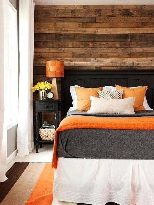 pared de madera, ropa de cama y lámpara naranja