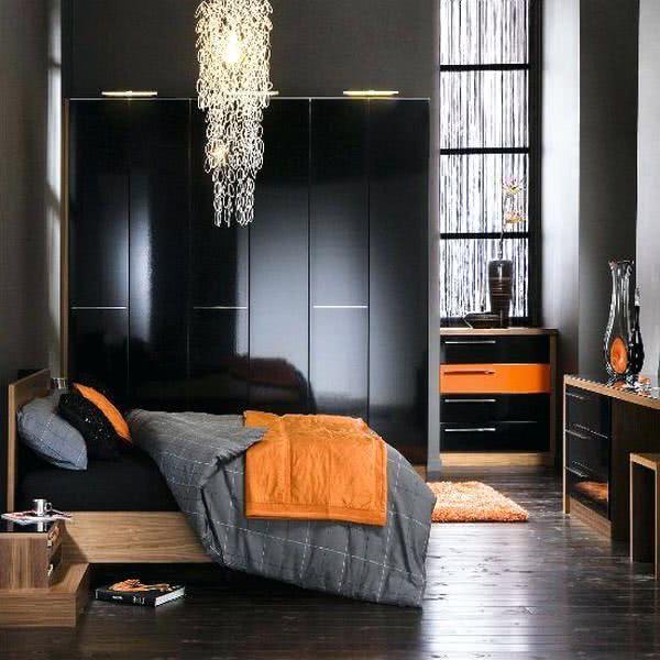 colcha naranja, cuarto con tonos de gris oscuro