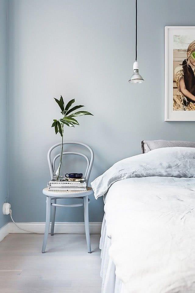 pared celeste claro, cama y suelo en tonos de blanco