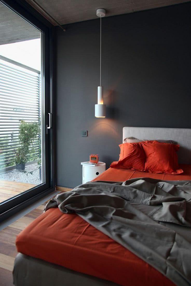 habitación gris, suelos de madera, sábanas y almohadas en naranja