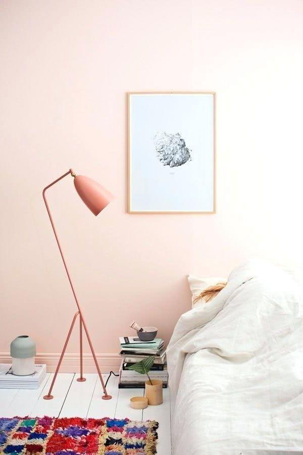 cuarto con pared rosa pastel salmón lámpara salmon cama beige y cuadro
