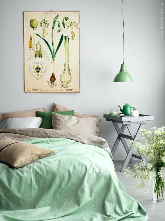 pared gris, cama verde pastel menta, lámpara, cojines y adornos verde menta