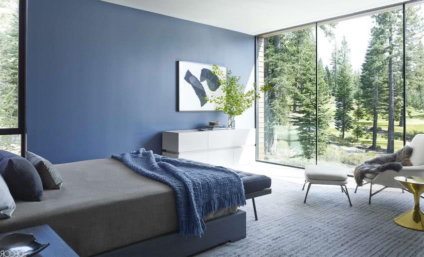 dormitorio con paredes azules, grandes ventanales, cama y sillones grises