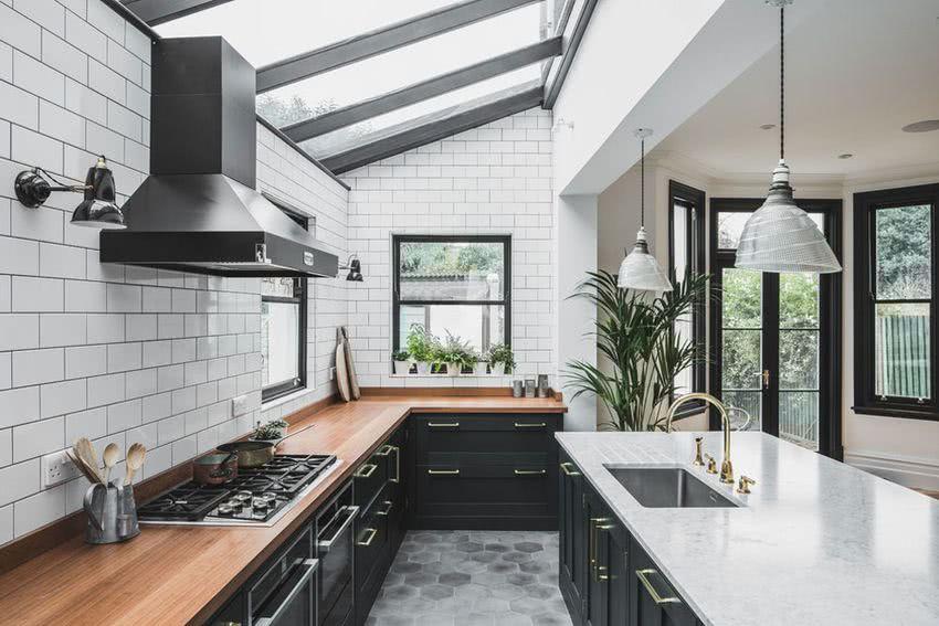 cocina con azulejos blancos de metro, muebles negros, encimera madera, ventanas al exterior